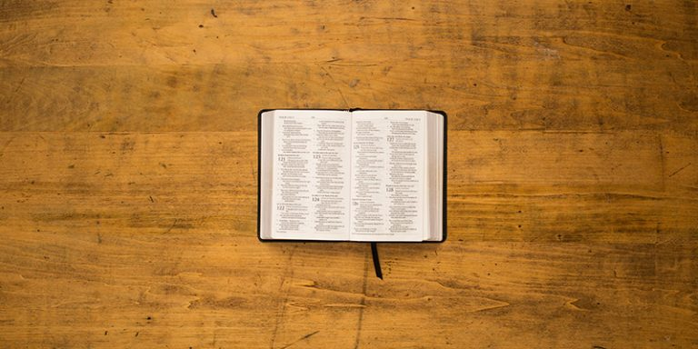 bible opened to psalms on wooden table
